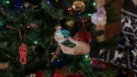 De moeder hangt het stuk speelgoed van de Kerstmisboom stock videobeelden