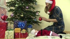 De moeder hangt het stuk speelgoed van de Kerstmisboom zuigelingsbaby in Kerstmiskleding stock videobeelden