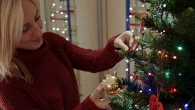 De moeder hangt het uitstekende nieuwe stuk speelgoed van de jaarboom op de tak van de Kerstmisboom stock footage