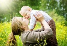 De moeder heft haar zoon op en kust hem op aardachtergrond Stock Foto's