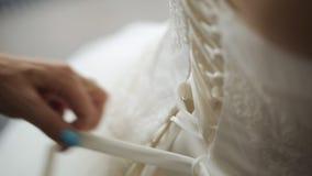 De moeder helpt haar dochter om stichtingskledingstuk op haar huwelijkskleding vast te maken stock footage