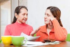 De moeder helpt volwassen dochter invult rekeningen Stock Afbeeldingen
