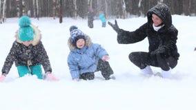 De moeder, het meisje en weinig jongen werpen op sneeuw tijdens sneeuwval in de winterpark stock footage