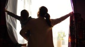 De moeder houdt een kind in de ochtend dichtbij het venster Vroeg in de ochtend openen zij de gordijnen, de de stralenpas van de  stock videobeelden
