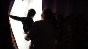 De moeder houdt een kind in de ochtend dichtbij het venster Vroeg in de ochtend openen zij de gordijnen, de de stralenpas van de  stock footage