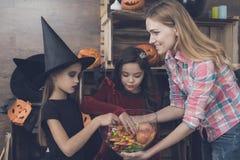 De moeder houdt een vaas met snoepjes voor kinderen gekleed in kostuums van monsters voor Halloween Royalty-vrije Stock Afbeelding