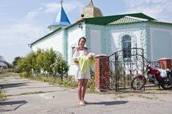 De moeder houdt haar baby wat een witte doopseltoga dichtbij kerk draagt royalty-vrije stock foto's