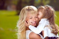 De moeder houdt haar dochter in haar wapens stock fotografie