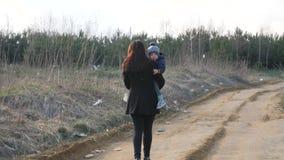 De moeder houdt haar kind in haar wapens, gaat langs de vuile weg van polyethyleenzakken stock video