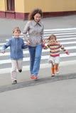 De moeder houdt hand van kinderen en de kruising van weg Stock Afbeelding