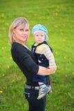 De moeder houdt kind in haar wapens bij weide Stock Afbeeldingen