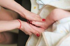 De moeder houdt voeten van pasgeboren baby stock fotografie