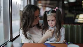 De moeder kalmeert en koestert een schreeuwend meisje Bij de stroom van dochterscheuren op het gezicht stock video