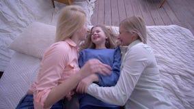 De moeder-kind verhouding, gelukkig mamma met dochters valt op bed tijdens van het pretlach en kietelende gevoel meisje