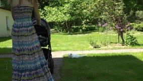 De moeder in kleding probeert om baby naar slaap in wandelwagen in tuin te sturen 4K stock footage