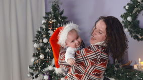 De moeder kust baby in Kerstmanhoed dichtbij Kerstboom stock video