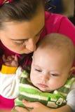 De moeder kust haar zoon Stock Afbeeldingen