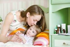 De moeder kust het zieke kind Stock Afbeeldingen