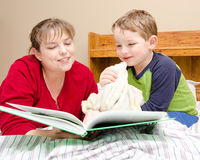 De moeder leest bedtijdverhaal aan jonge jongen Stock Foto