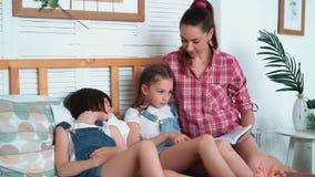 De moeder leest boek aan haar dochters en zij vallen in slaap op bed, gelukkige familie stock footage