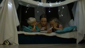 De moeder leest een bedtijdverhaal voor kinderen stock video