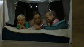 De moeder leest een bedtijdverhaal voor kinderen stock videobeelden