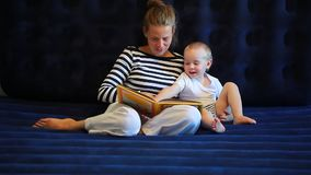 De moeder leest een boek aan een babyzitting op een matras stock video