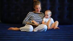 De moeder leest een boek aan een babyzitting op een matras stock videobeelden