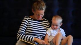 De moeder leest een boek aan een babyzitting op een matras stock footage