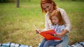 De moeder leest een boek met haar dochter in het park stock videobeelden