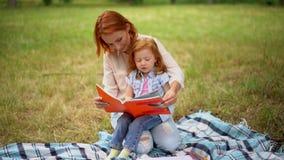 De moeder leest een boek met haar dochter in het park stock footage
