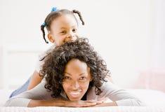 De moeder legt op bed met speelse dochter Royalty-vrije Stock Afbeeldingen