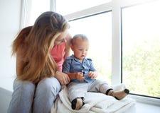 De moeder leidt babyzoon op thuis, ouderschapverhouding stock afbeeldingen