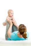 De moeder met baby doet gymnastiek- oefeningen Royalty-vrije Stock Foto's