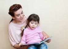 De moeder met de dochter las het boek Stock Foto