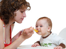 De moeder met de lepel voert haar braaf baby Royalty-vrije Stock Foto's