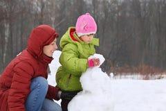 De moeder met dochter beeldhouwt sneeuwman Stock Afbeeldingen