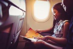 De moeder met dochter zit op hun plaats in vliegtuig royalty-vrije stock afbeelding