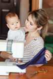 De moeder met een baby toont haar werk, die thuis naaien Het opheffen van kinderen, kinderverzorging, kindermeisje Stock Foto
