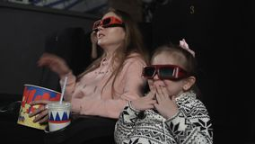 De moeder met haar dochter let op 3d film in bioskoop Emotie - verrassing stock videobeelden