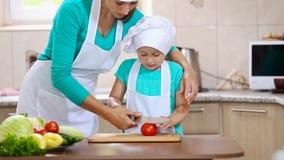 De moeder met haar dochter sneed tomaat stock video