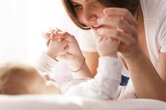 De moeder met haar pasgeboren zoon legt op het bed in de stralen van zonlicht royalty-vrije stock afbeelding