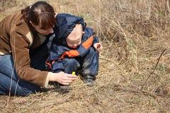 De moeder met kind kijkt op eerste bloem in de lente Royalty-vrije Stock Afbeelding