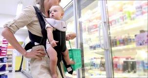 De moeder met kind in rugzak kiest producten stock videobeelden