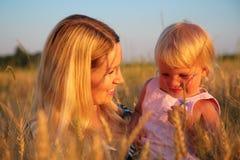 De moeder met kind zit op wheaten gebied