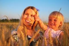 De moeder met kind zit op wheaten gebied met cornf