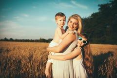 De moeder met kinderen gaat op gebied Stock Afbeeldingen