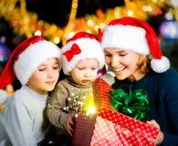 De moeder met kinderen opent de doos met Kerstmisgiften Stock Afbeeldingen