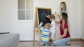 De moeder met kinderen trekt krijt op een bord stock videobeelden