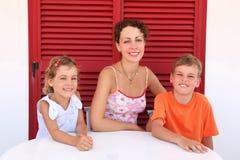 De moeder met kinderen zit dichtbij gesloten deur aan lijst Stock Foto
